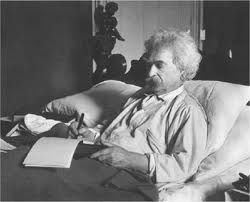 Mark Twain writing in bed