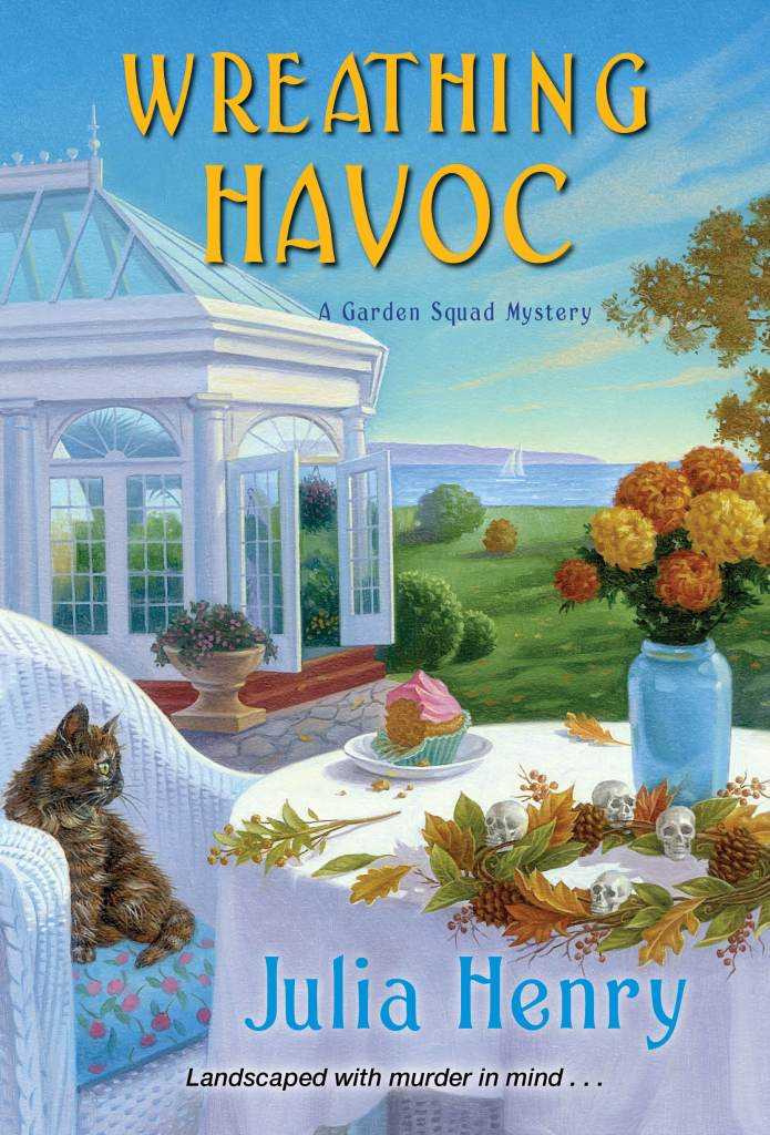 cover for Wreathing Havoc by Julia Henry. Scene includes a greenhouse, view of the ocean. On a table is a partially eaten cupcake, and wreath. A cat looks on.